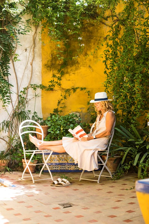 Seville Woman With White Hat Sitting In Grotto Reading A Book