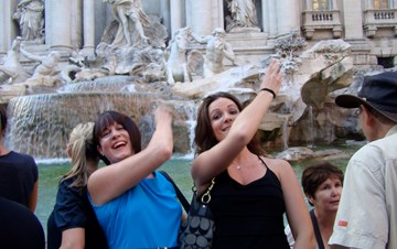 Two women throwing coins into Trevi Fountain in Rome, Italy
