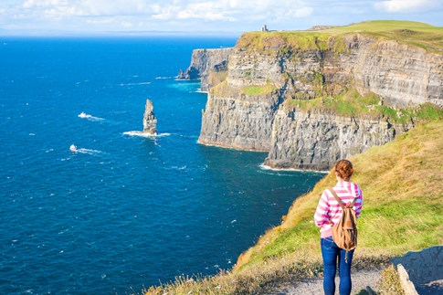 Woman looking out over Cliffs of Moher, Ireland
