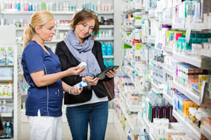 two women looking at medications in pharmacy