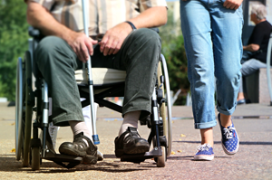 man in wheelchair with cane, young girl walking next to him