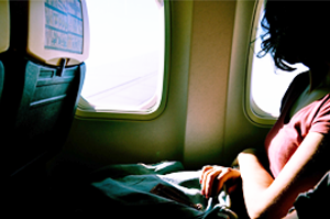 woman on airplane looking out window