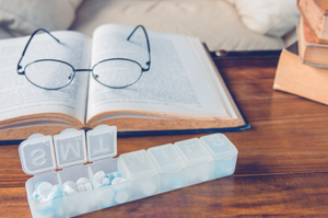 reading glasses and pill organizer